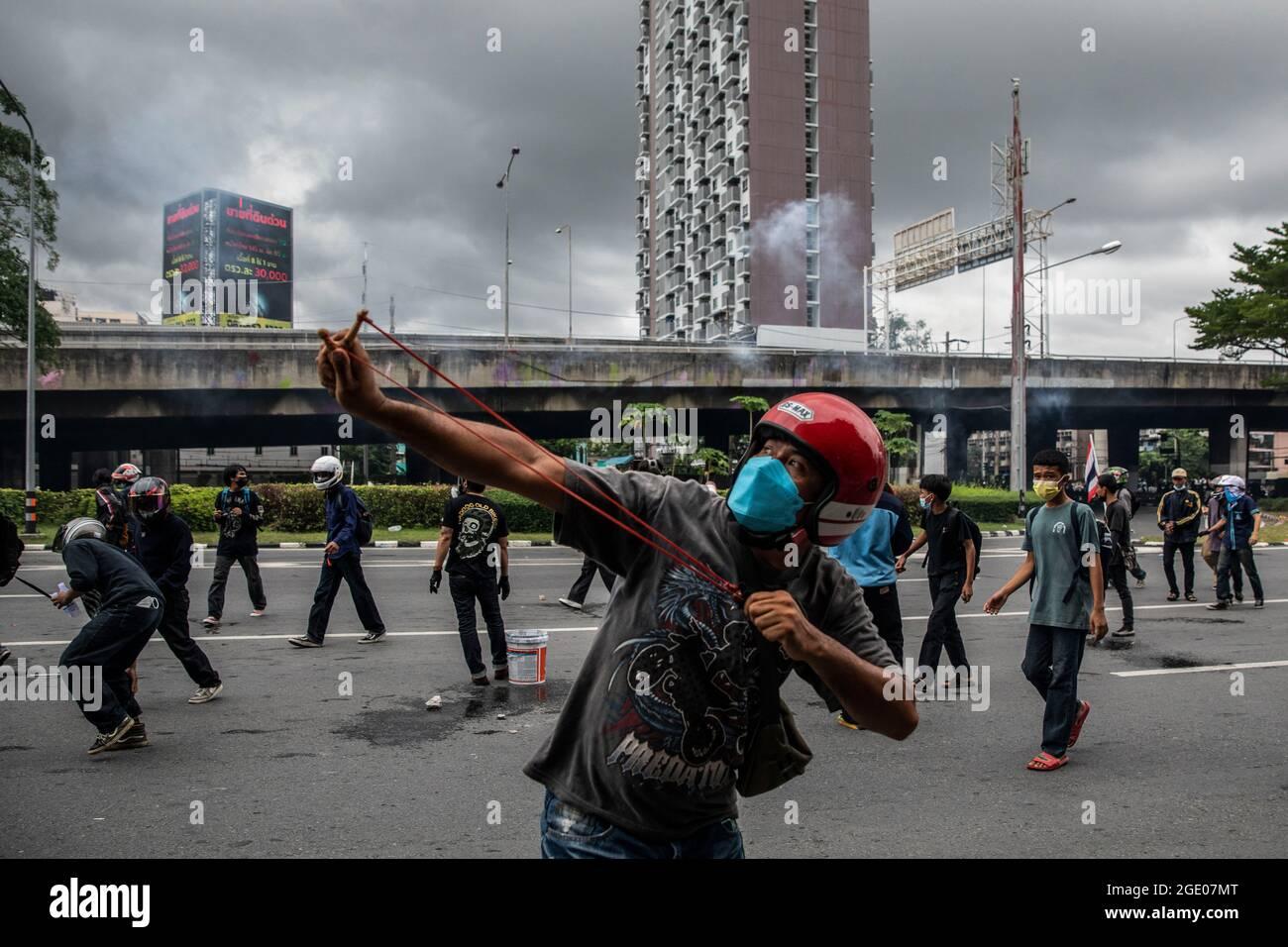 Bangkok, Thailand. August 2021. Ein Protesten für die Demokratie schießt am 15. August 2021 bei Zusammenstößen mit der Polizei in Bangkok, Thailand, eine Schleuder. Eine stadtweite Motorradkundgebung, die hauptsächlich aus Red Shirts besteht und von dem ehemaligen Gesetzgeber Nattawut Saikuar geleitet wird, fuhr friedlich durch Bangkok und forderte die Demonstranten auf, nicht gewalttätig zu werden. Einige Demonstranten, vor allem Jugendgruppen wie REDEM, versuchten jedoch erneut, die Residenz des thailändischen Premierministers Prayuth Chan-Ocha zu erreichen, was unweigerlich zu Zusammenstößen mit den Strafverfolgungsbehörden führte. Kredit: ZUMA Press, Inc./Alamy Live Nachrichten Stockfoto