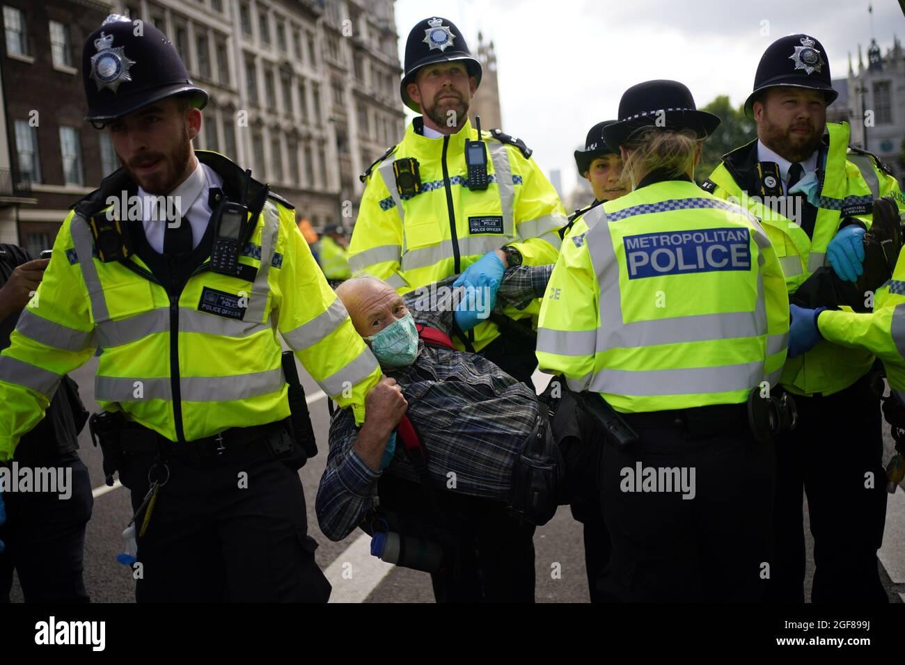 Die Polizei bringt einen Demonstranten während eines Protestes von Mitgliedern des Extinction Rebellion in Whitehall, im Zentrum von London, mit. Bilddatum: Dienstag, 24. August 2021. Stockfoto