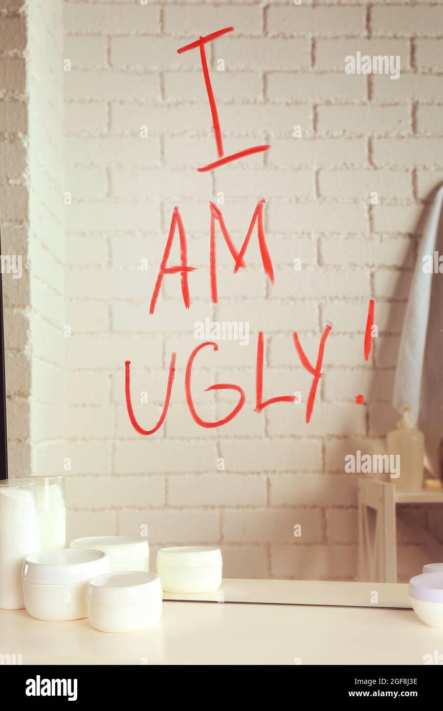 Text ICH BIN HÄSSLICH auf Spiegel im Badezimmer geschrieben ...