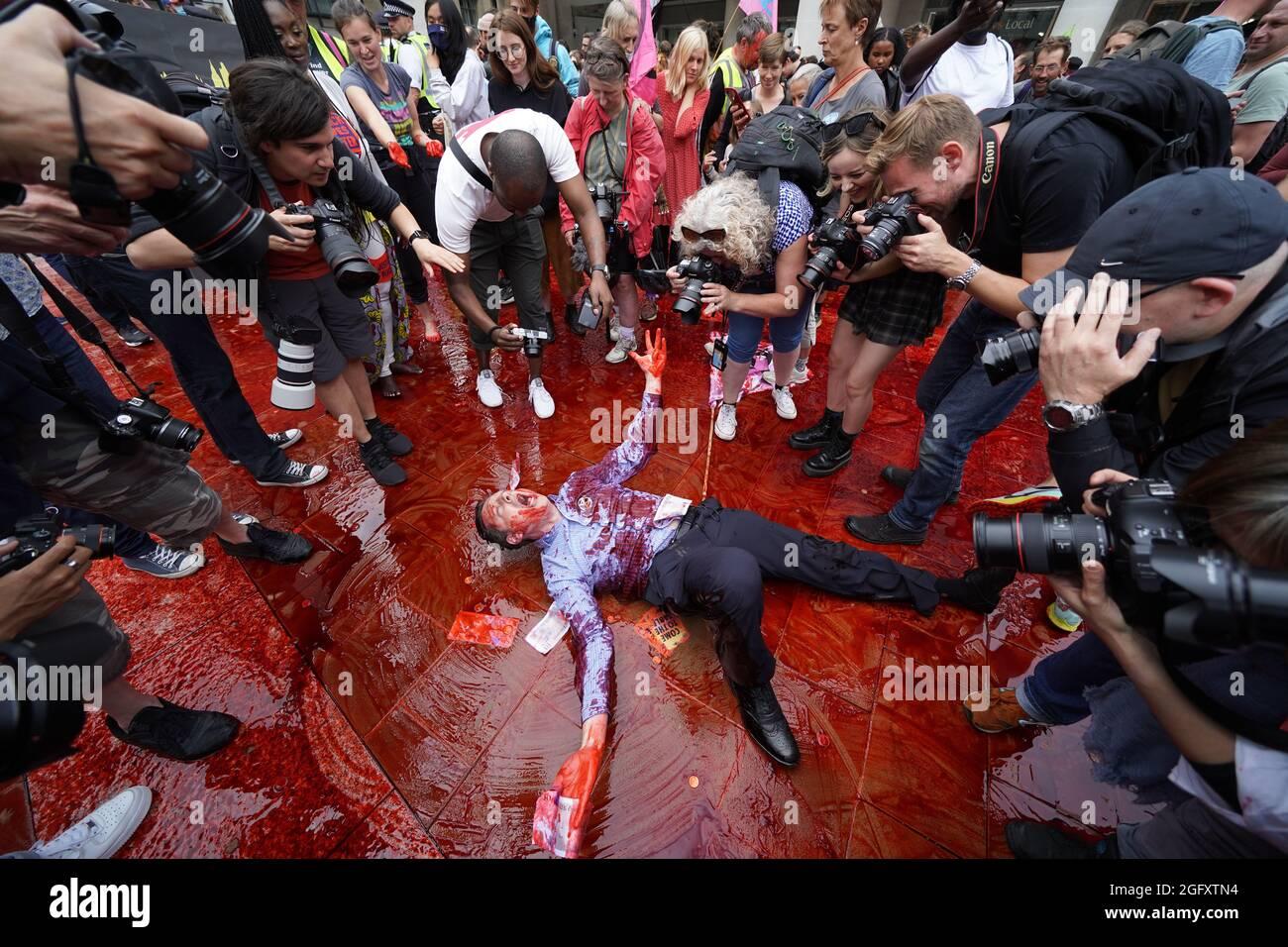 Ein Mitglied der Extinction Rebellion rollt in gefälschtem Blut auf dem Peternoster Square im Zentrum von London herum. Bilddatum: Freitag, 27. August 2021. Stockfoto