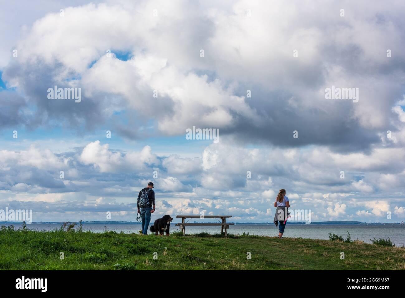 Ein Mann und eine Frau mit Hund beim Spaziergang an der