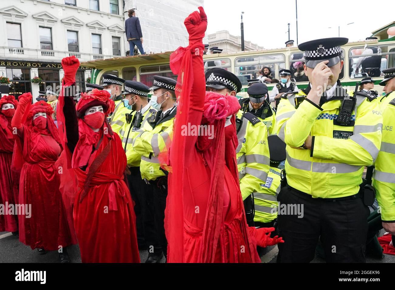 Polizei und Demonstranten mit einem Bus, der auf der London Bridge im Zentrum von London während eines Protestes von Mitgliedern der Extinction Rebellion geparkt wurde. Bilddatum: Dienstag, 31. August 2021. Stockfoto