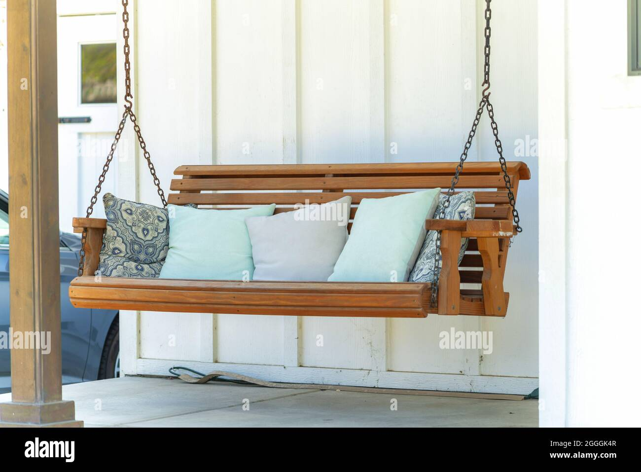 Eine Schaukel auf der Veranda mit bequemen Kissen auf der Terrasse ...