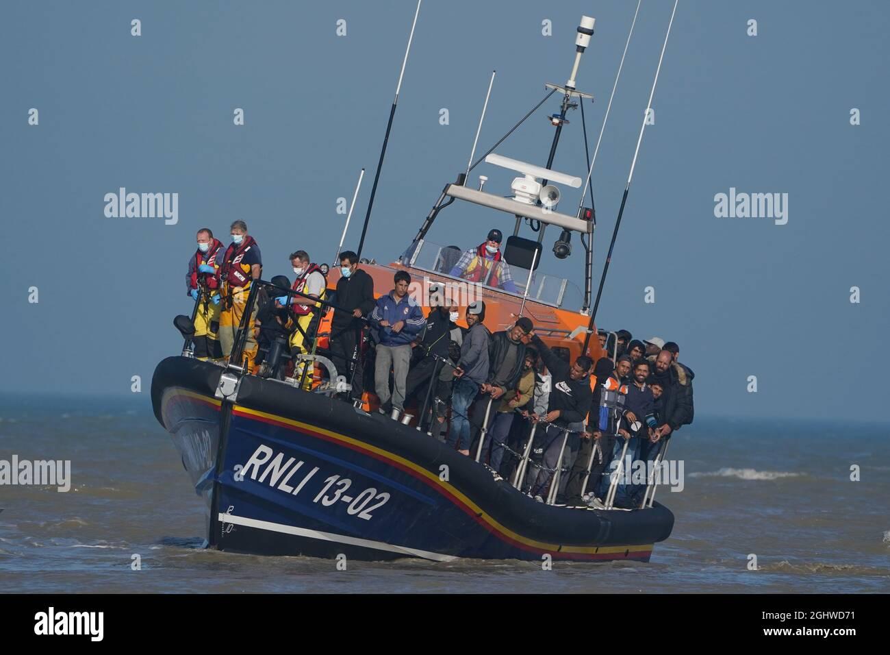 Eine Gruppe von Menschen, die als Migranten gelten, wird vom lokalen Rettungsboot in Dungeness in Kent an Land gebracht, nachdem sie nach einem Vorfall mit einem kleinen Boot im Kanal abgeholt wurde. Bilddatum: Dienstag, 7. September 2021. Stockfoto