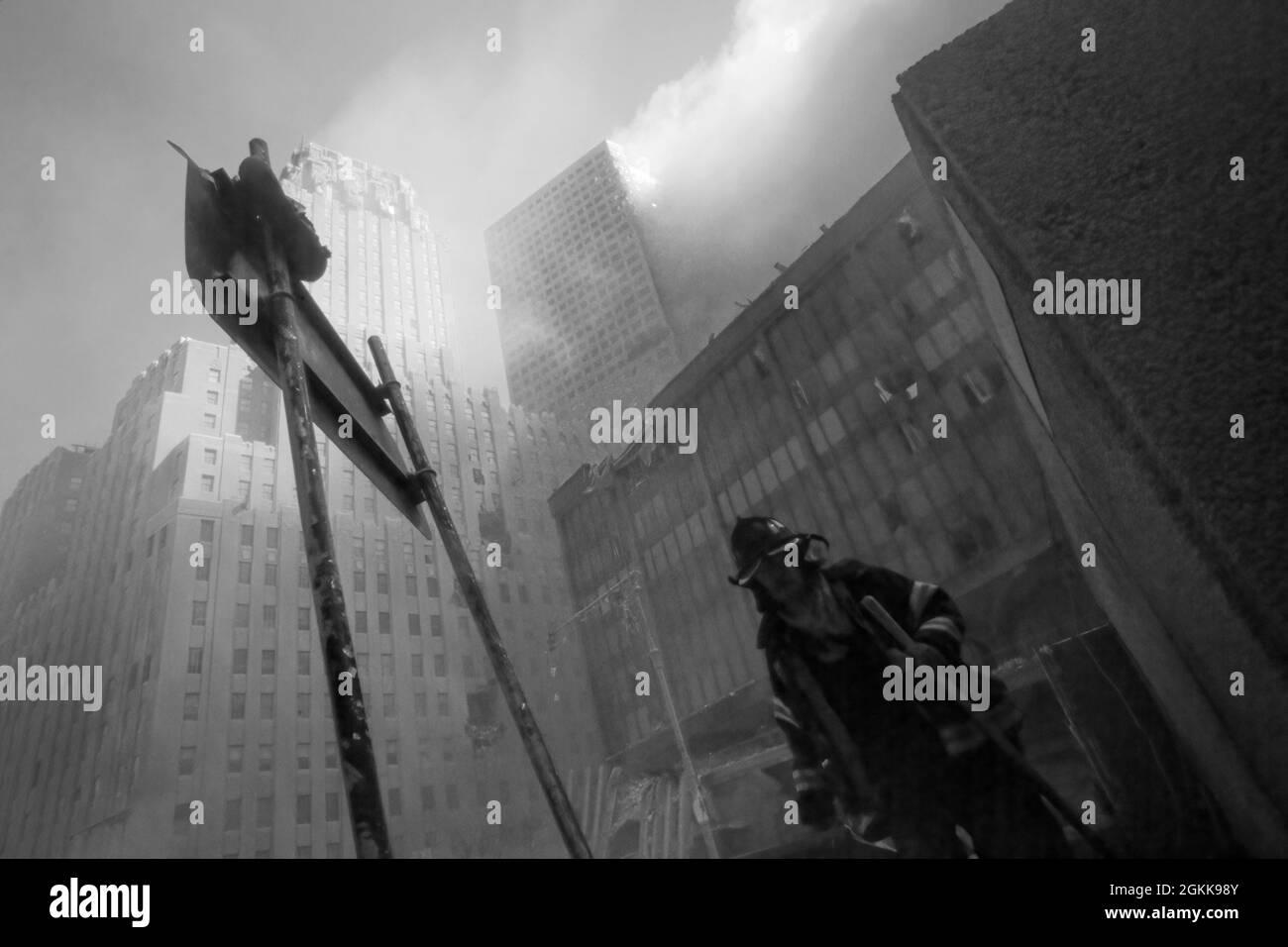 FDNY-Feuerwehrmann, der aus dem Rauch von New York City auftaucht, während die Twin Towers während des Angriffs von islamischen Terroristen am 11. September 2021 brennen. (USA) Stockfoto