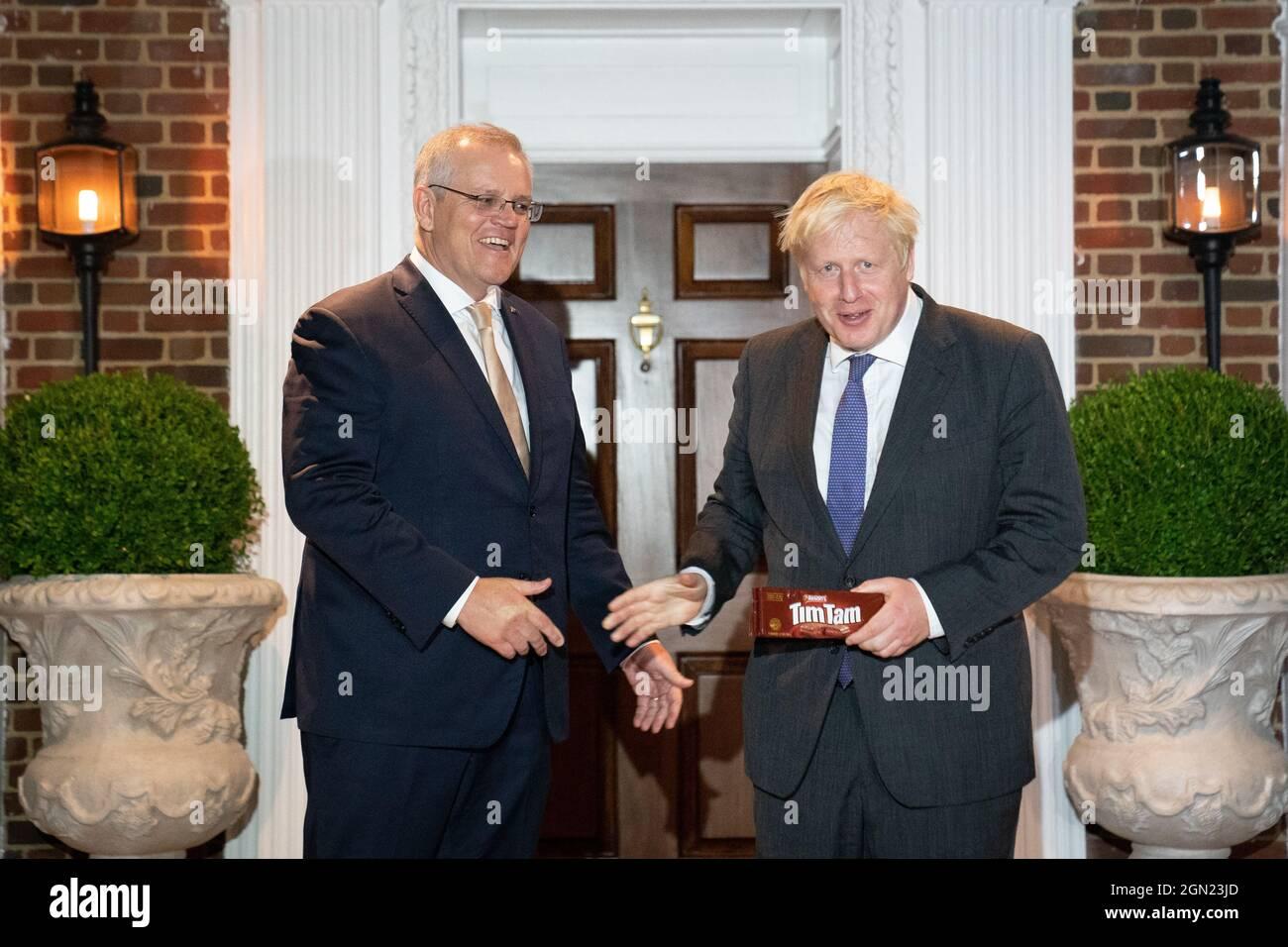 Premierminister Boris Johnson erhält ein Paket mit dem australischen Snack, Tim Tams, als er von seinem australischen Amtskollegen Scott Morrison in Washington DC während seines Besuchs in den Vereinigten Staaten zur Generalversammlung der Vereinten Nationen begrüßt wird. Bilddatum: Dienstag, 21. September 2021. Stockfoto