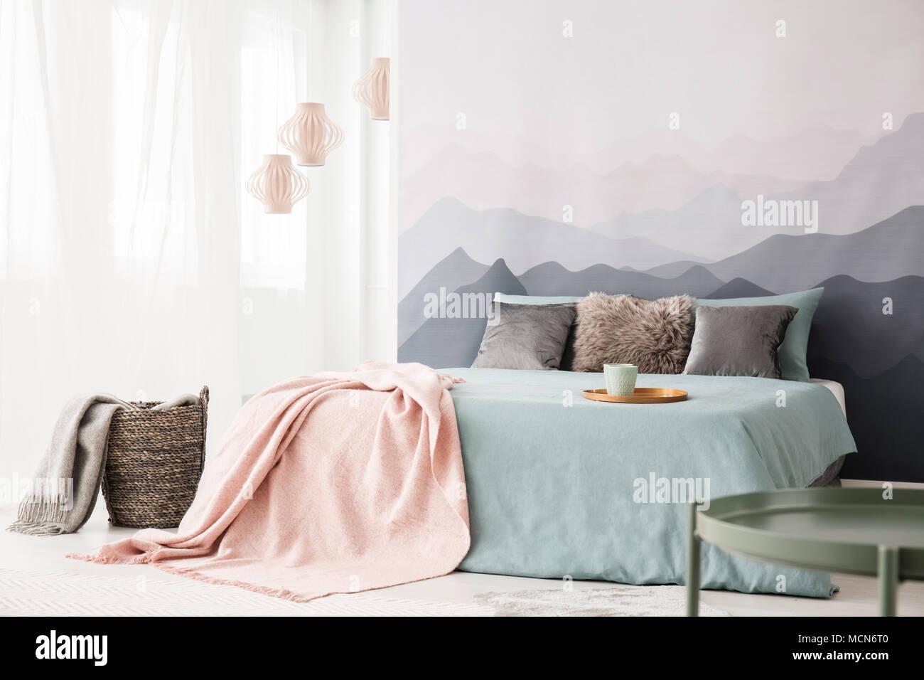 Warenkorb neben dem bett mit rosa decke in pastelltönen schlafzimmer