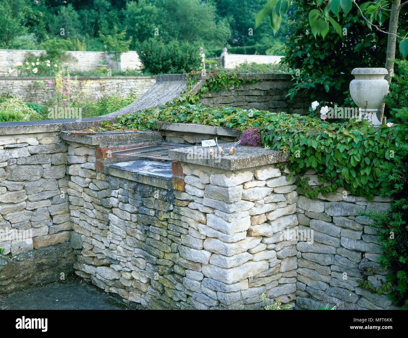 hinterhof detail einer mit wein bewachsenen stein grill stockfoto