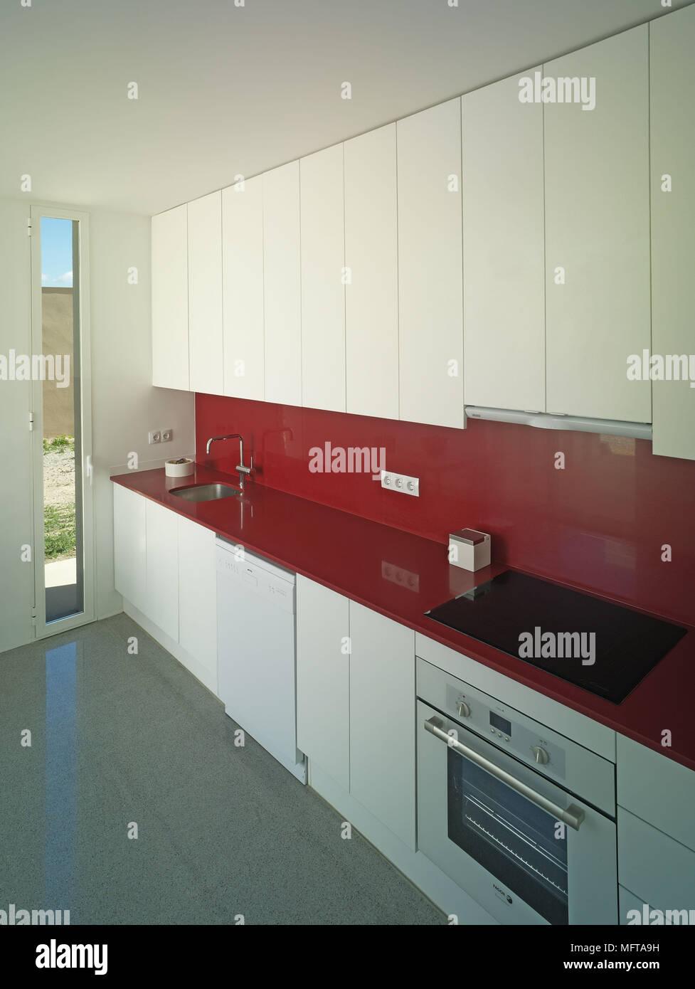 Spüle und Kocher in Rot auf der Arbeitsplatte in der Küche gesetzt ...