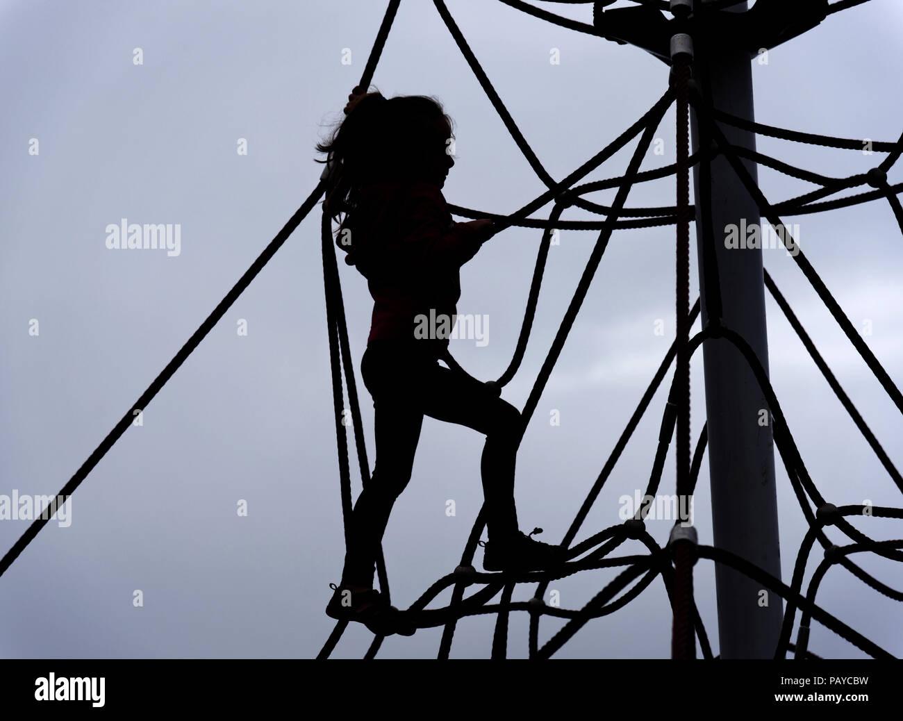 Klettergerüst Aus Seilen : Die silhouette eines jungen mädchens 6 jahre alt auf einem seil