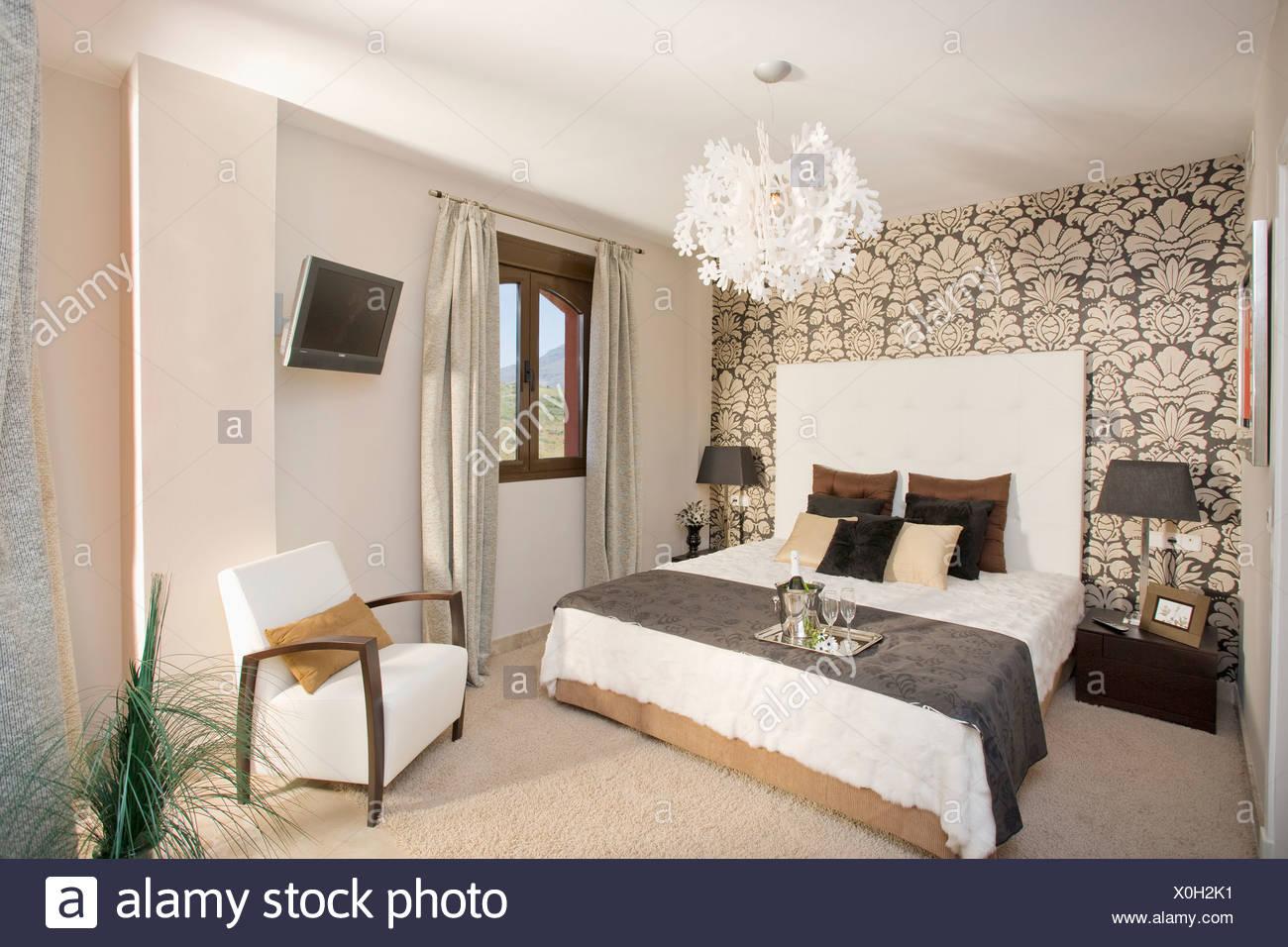 Schwarz / weiß gemusterten Tapeten an Wand hinter dem Bett mit ...