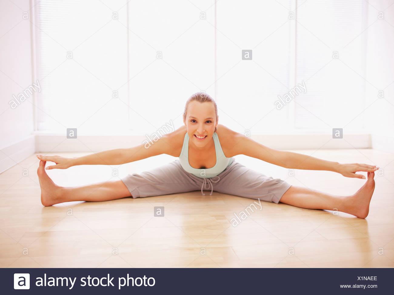 Porträt Der Lächelnde Frau Mit Gespreizten Beinen Dehnen Stockfoto