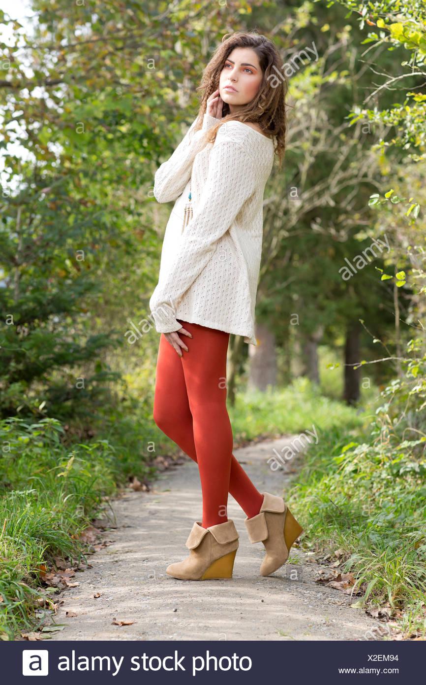 ff5365bec674 Junge Frau trägt einen langen weißen Pullover und rote Strumpfhose im freien