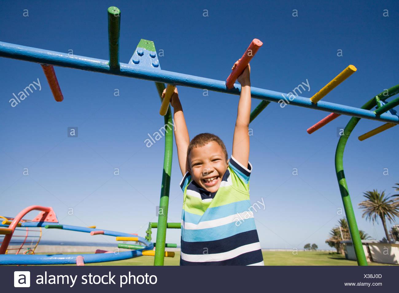 Klettergerüst Am Hang : Young boy hängen klettergerüst durch seine hände zur Übung am