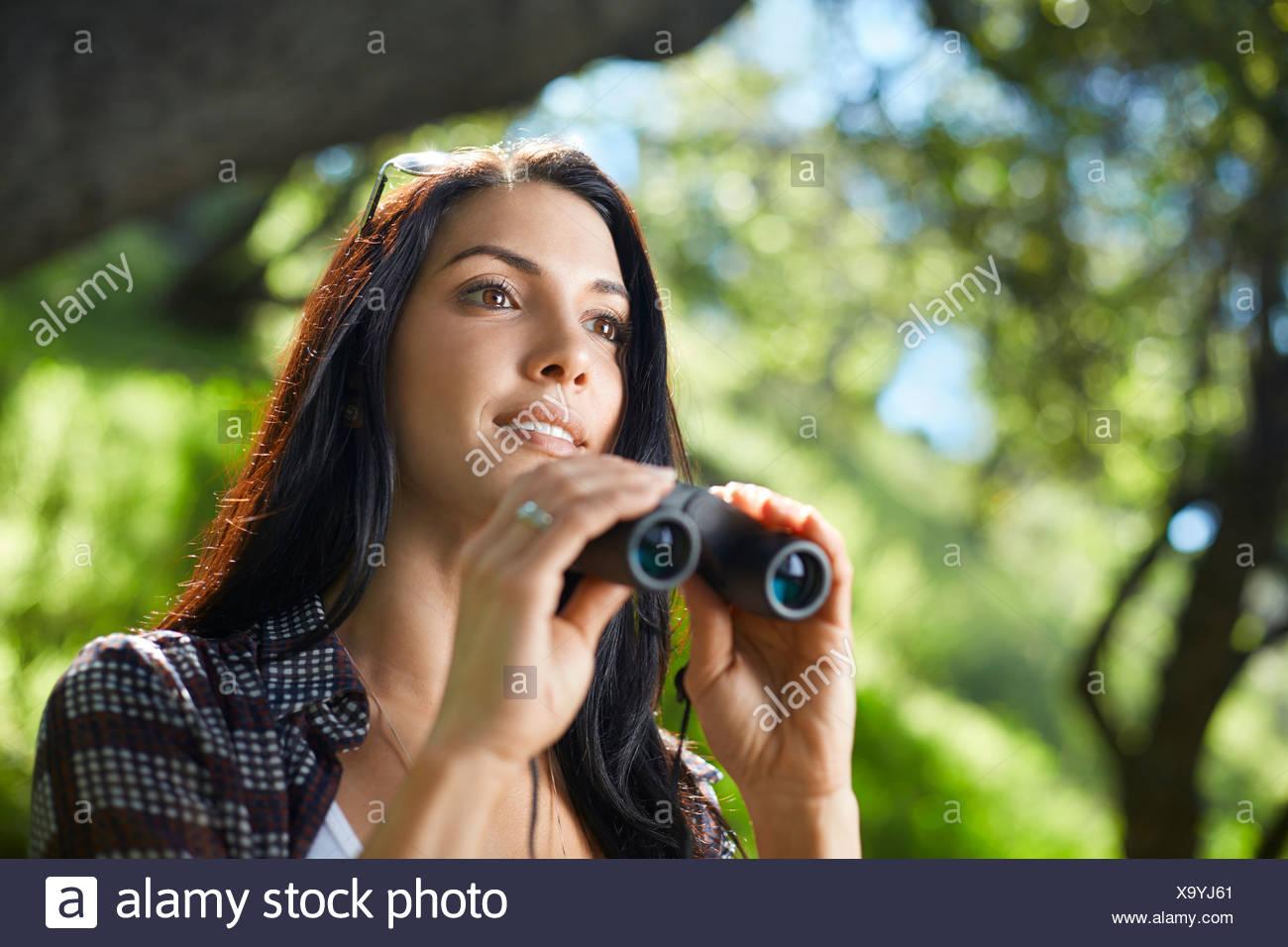 Mitte erwachsene frau mit fernglas vogelbeobachtung im wald
