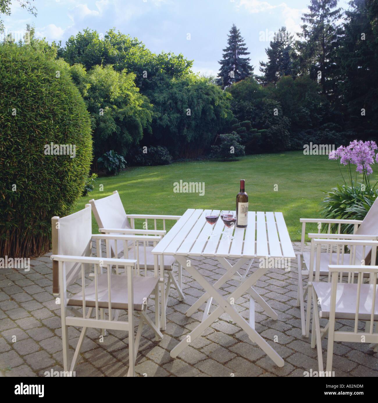 Weiße Gartenmöbel auf gepflasterte Terrasse mit Blick auf Rasen im ...