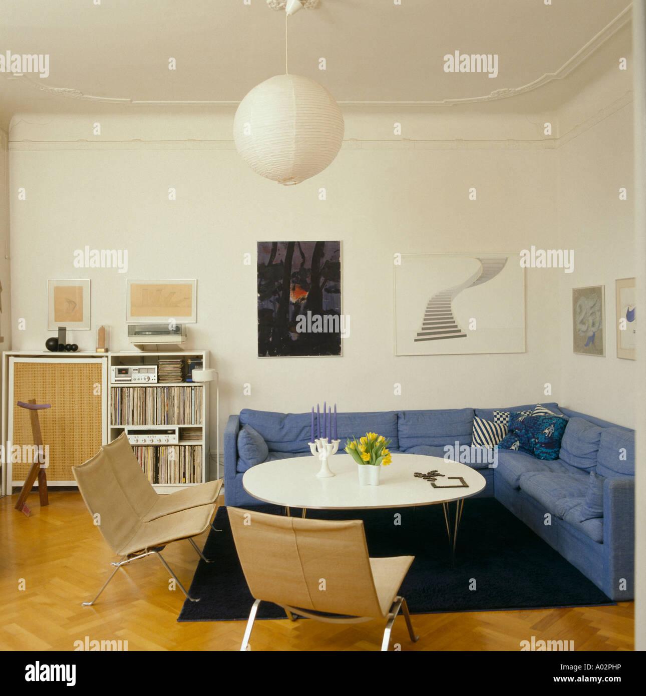 Blau L-förmigen Sofa und Stühle am weißen Rundtisch in kleinen ...
