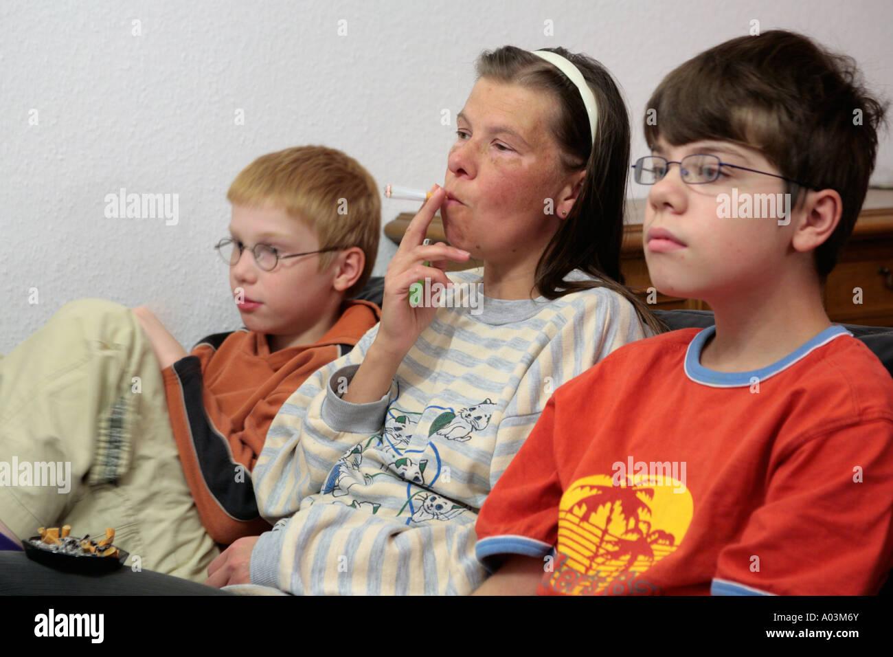 Mutter Rauchen beim Fernsehen mit ihren Kindern Stockbild