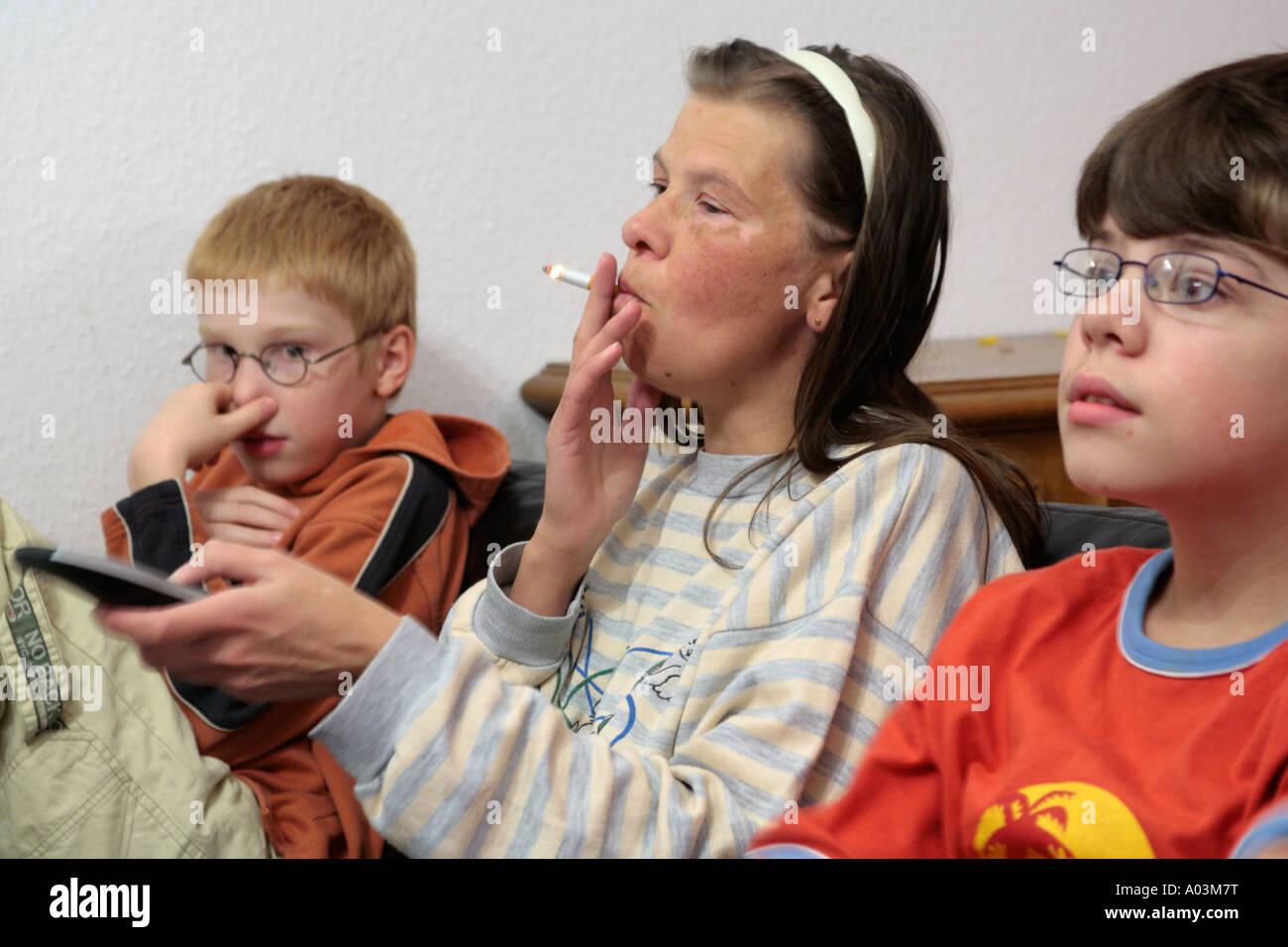 Eine Mutter raucht eine Zigarette beim Fernsehen mit ihren Kindern Stockbild