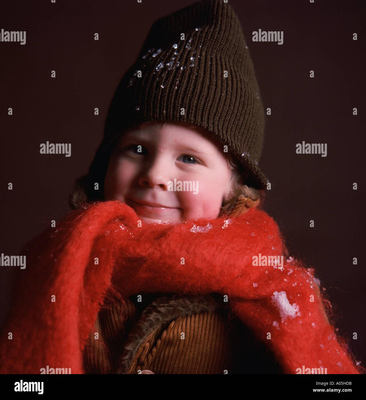 Nahaufnahme eines jungen tragen eine Wintermütze und einen großen roten Schal mit einige Schneeflocken auf ihn Stockfoto