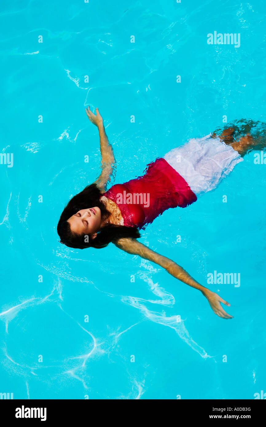 Teengirl schwimmt auf dem Rücken in einem Schwimmbad mit