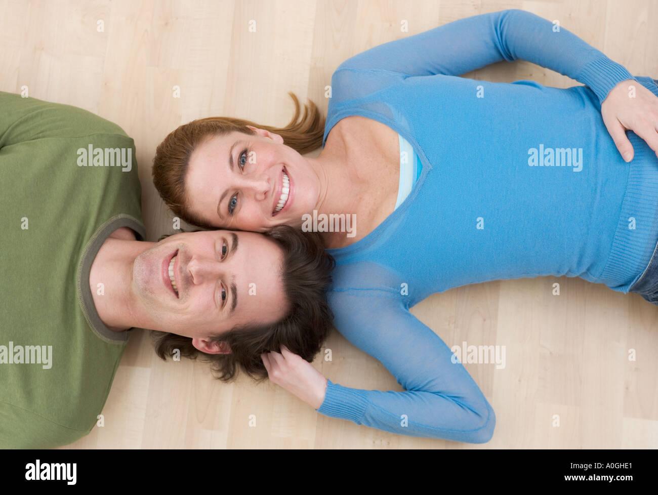 Lächelnde paar liegen auf Holzboden Stockbild