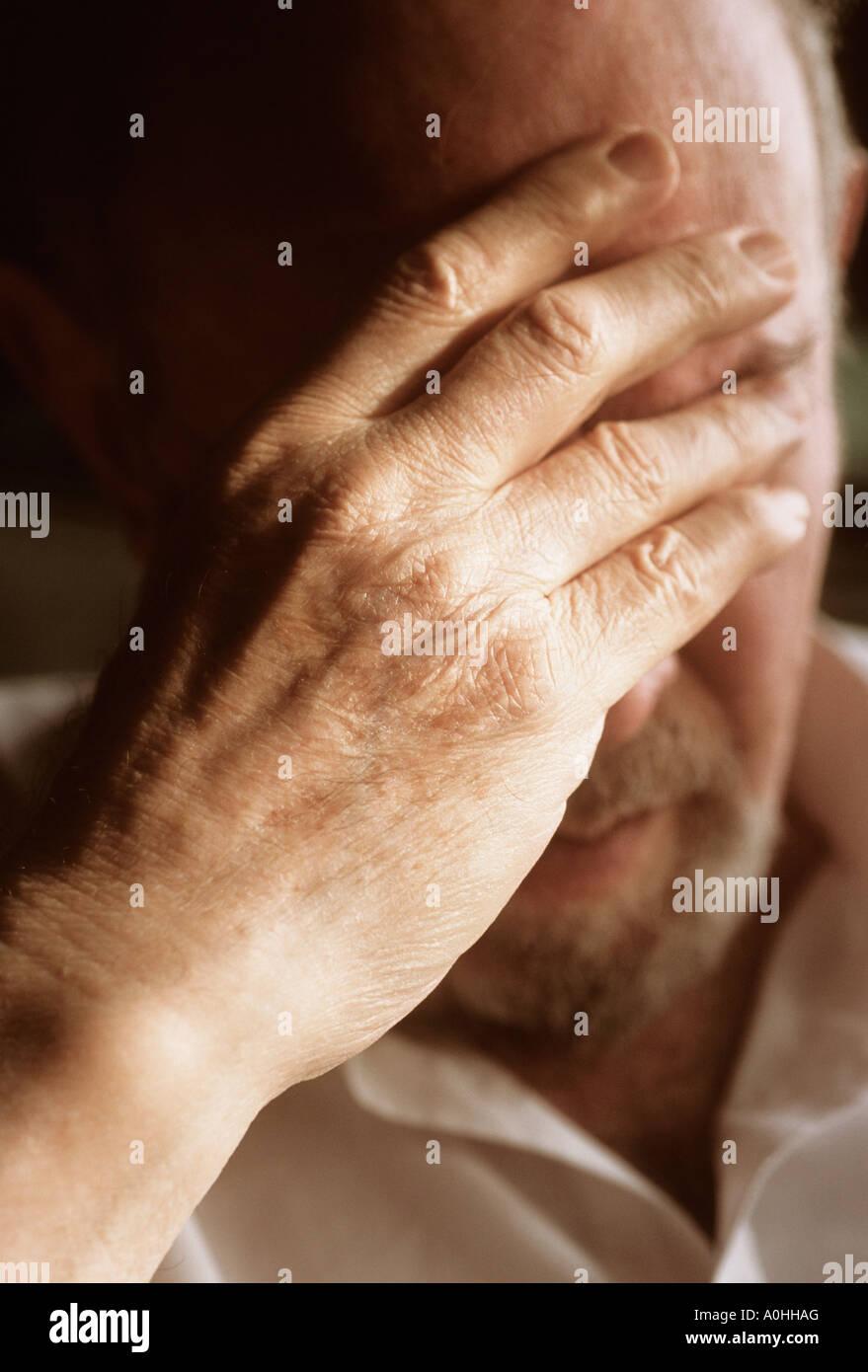 Nahaufnahme reifer Mann mit seiner Hand an den Kopf müde niedergeschlagen zeigen Schmerzen leiden unglücklich Stockbild