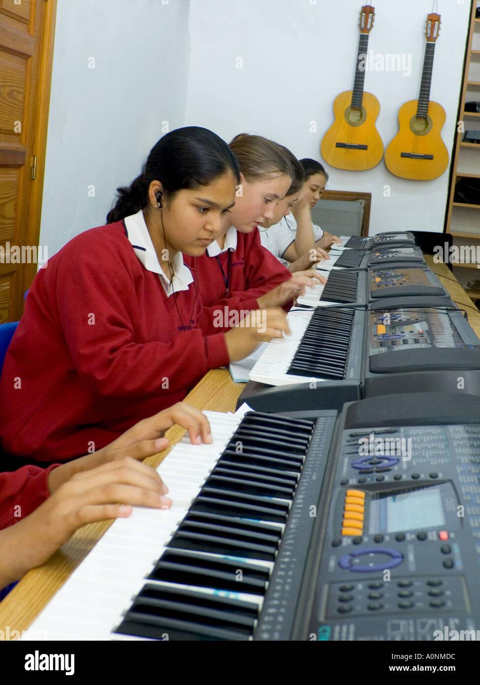 MUSIKUNTERRICHT TASTATUREN Teenage-Studenten tragen Kopfhörer üben & komponieren Gemeinsam Waagen auf elektronischen Klavieren im Klassenzimmer der Schulmusik spielen Stockfoto