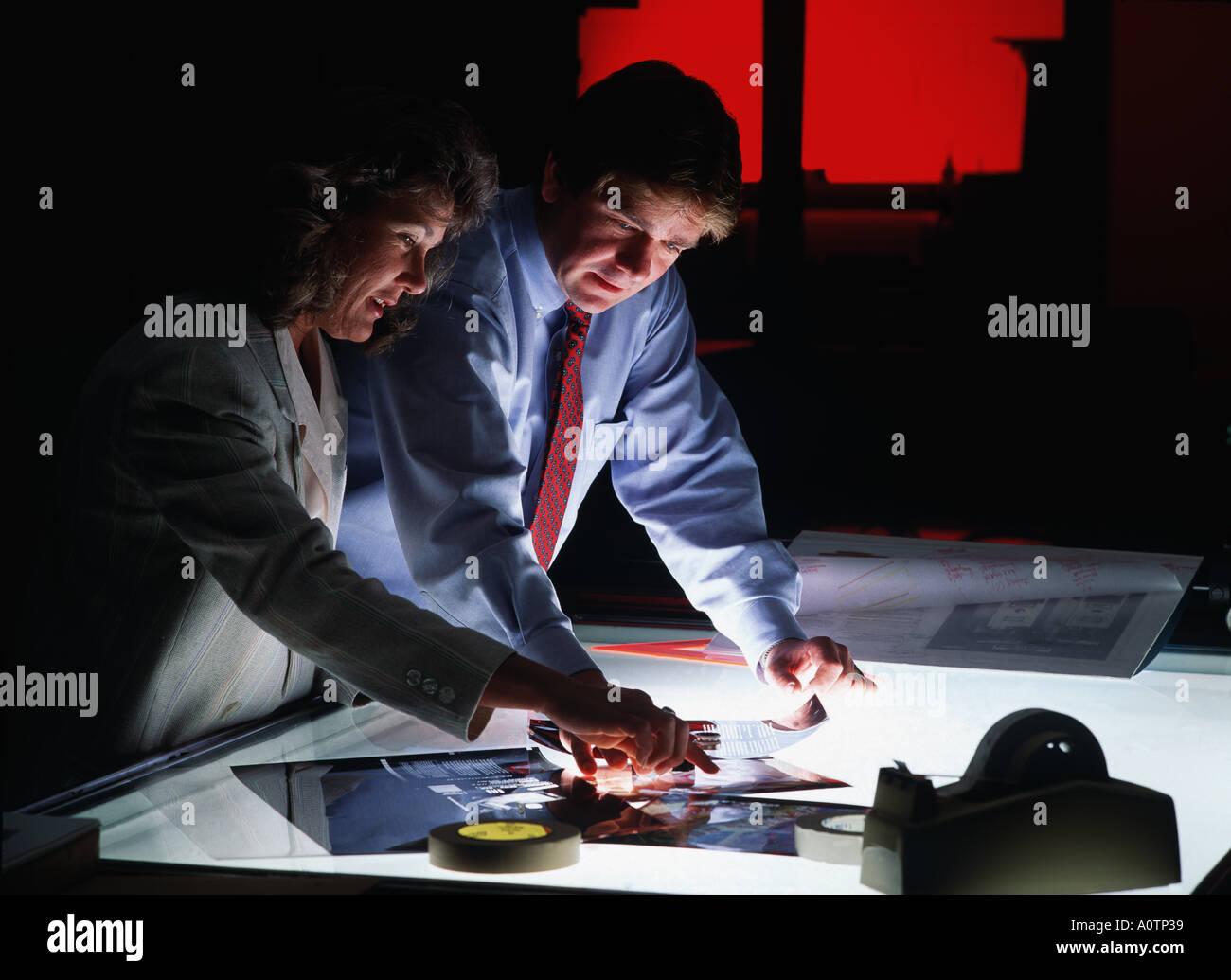 Drucken Verkäufer und Werbung Executive untersuchen Sie die Transparentfolien auf eine Druckvorstufe Lightbox Stockbild