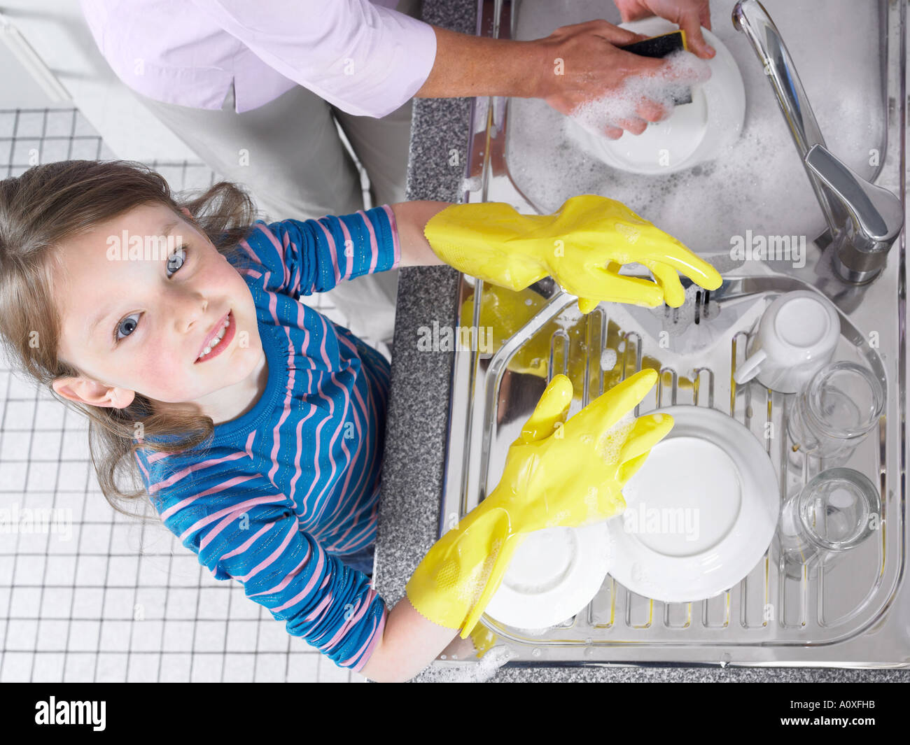 Mädchen mit Abwasch helfen Stockfoto