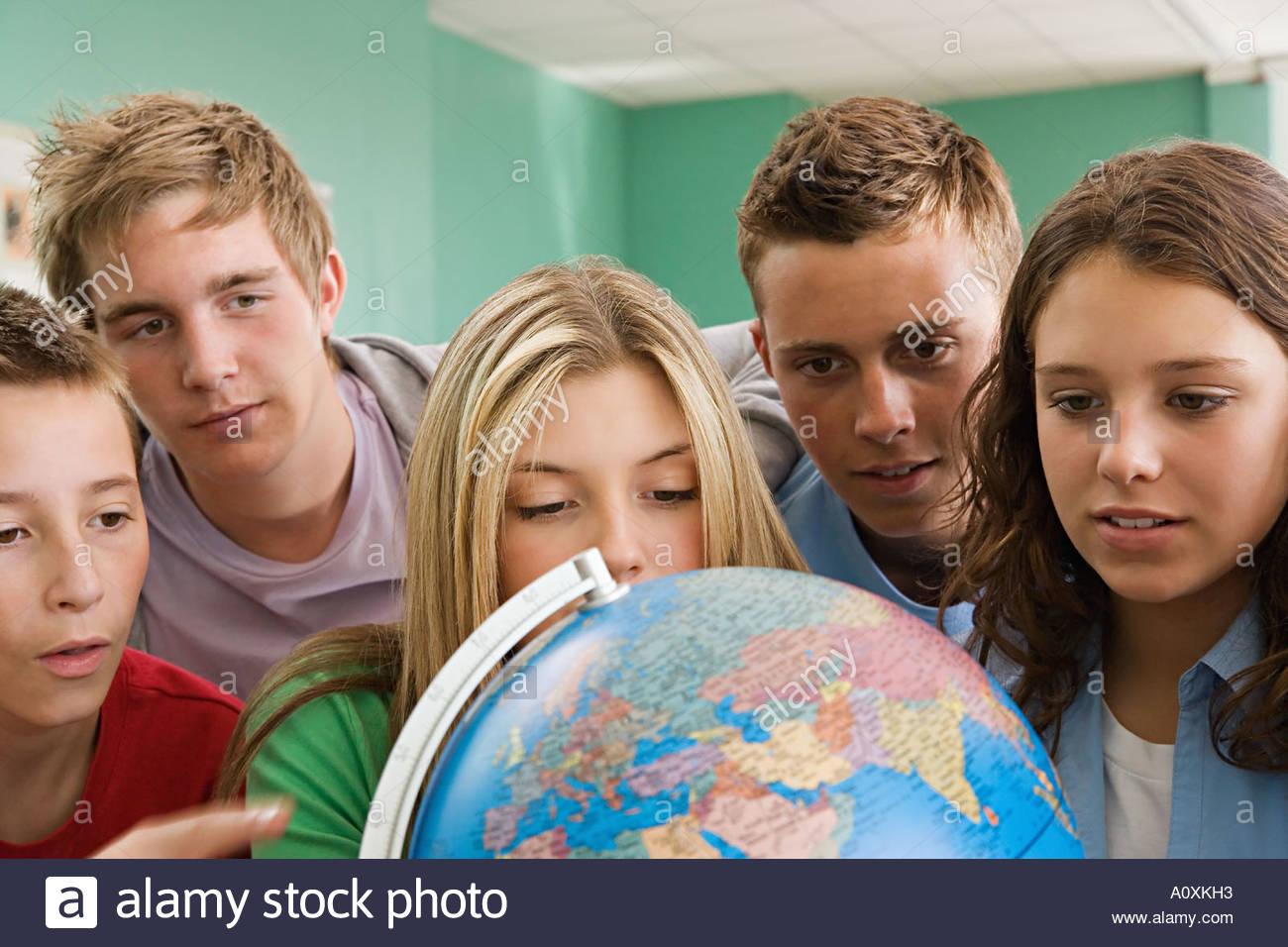 Schülerinnen und Schüler einen Globus betrachten Stockbild