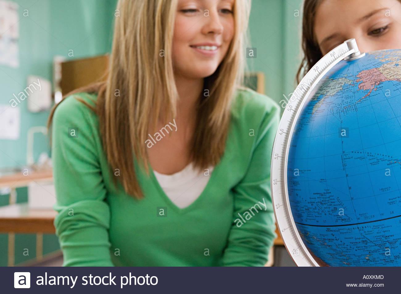 Mädchen auf der Suche auf einem Globus Stockbild