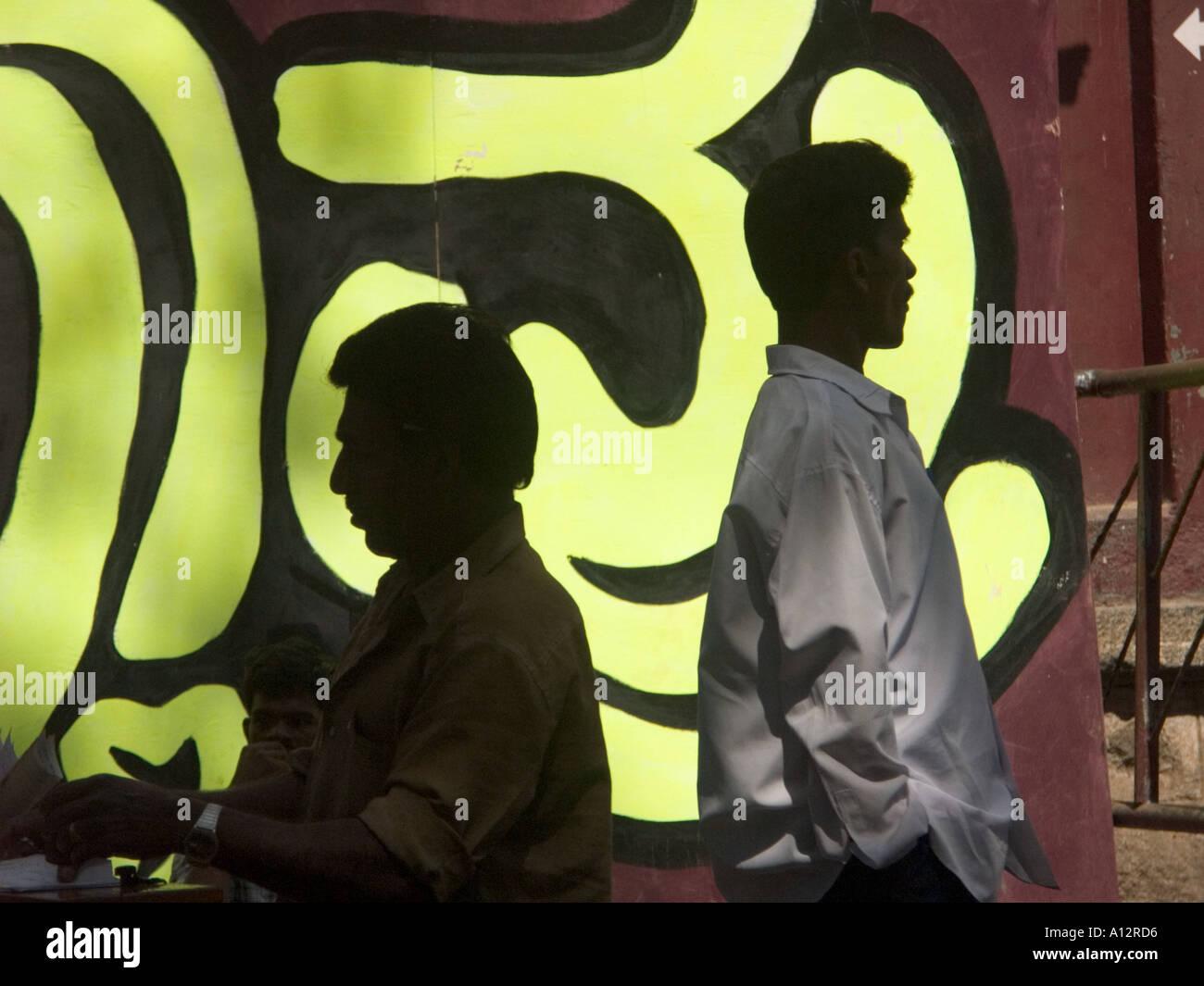 Männer stehen vor einem indischen Film-Plakat Stockbild