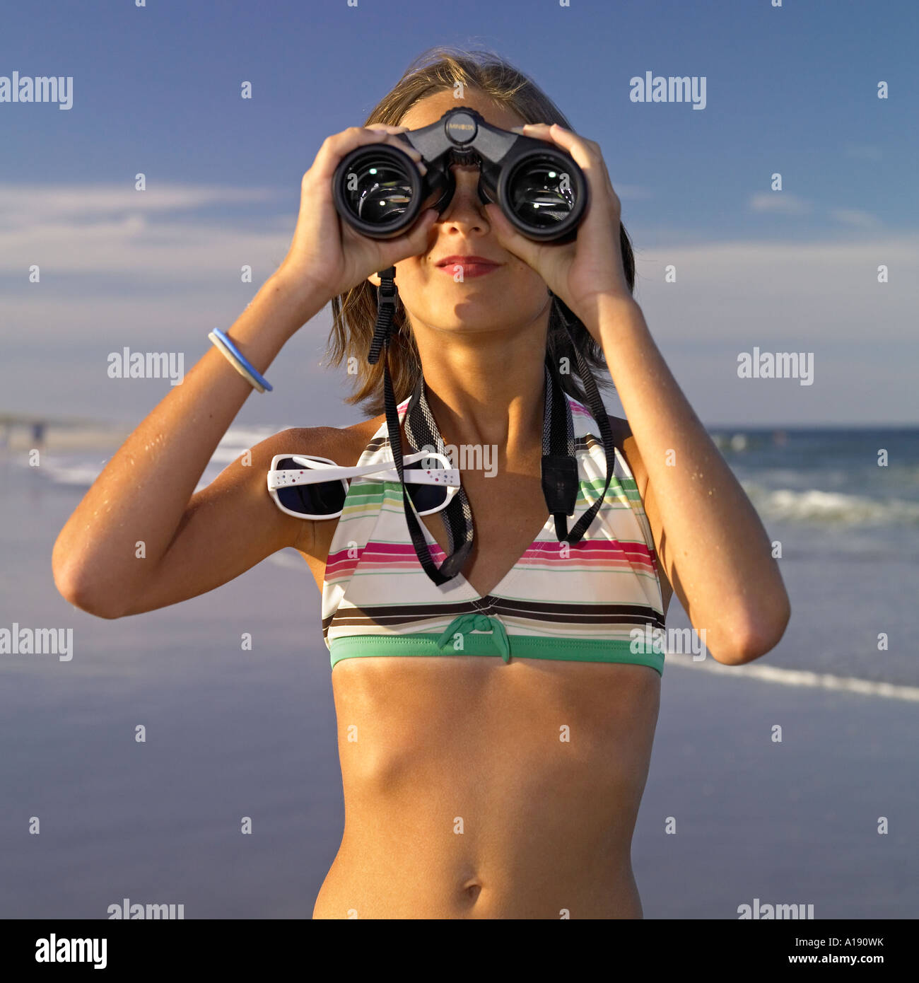 junges Mädchen in gestreiften Badeanzug am Strand, Blick durch ein Fernglas Stockbild