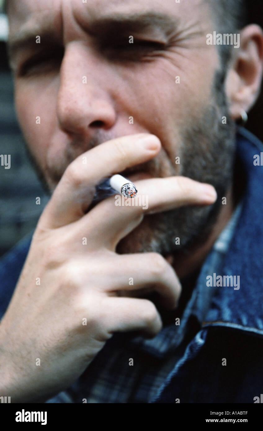 Man raucht eine Zigarette Stockbild