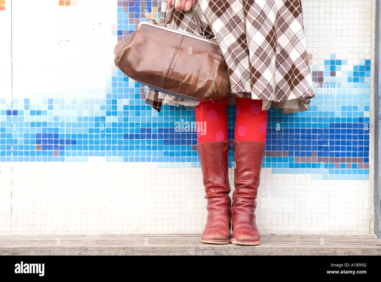 einen verkürzten Blick auf eine weibliche Beine stehen gegen eine moderne Wand bedeckt mit eleganten bunten Stockbild