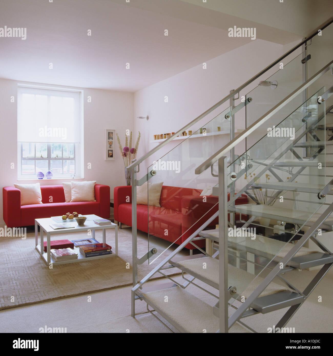 modernes wohnzimmer mit treppe : Modernes Wohnzimmer Mit Glas Treppe Und Roten Sofas Stockfoto