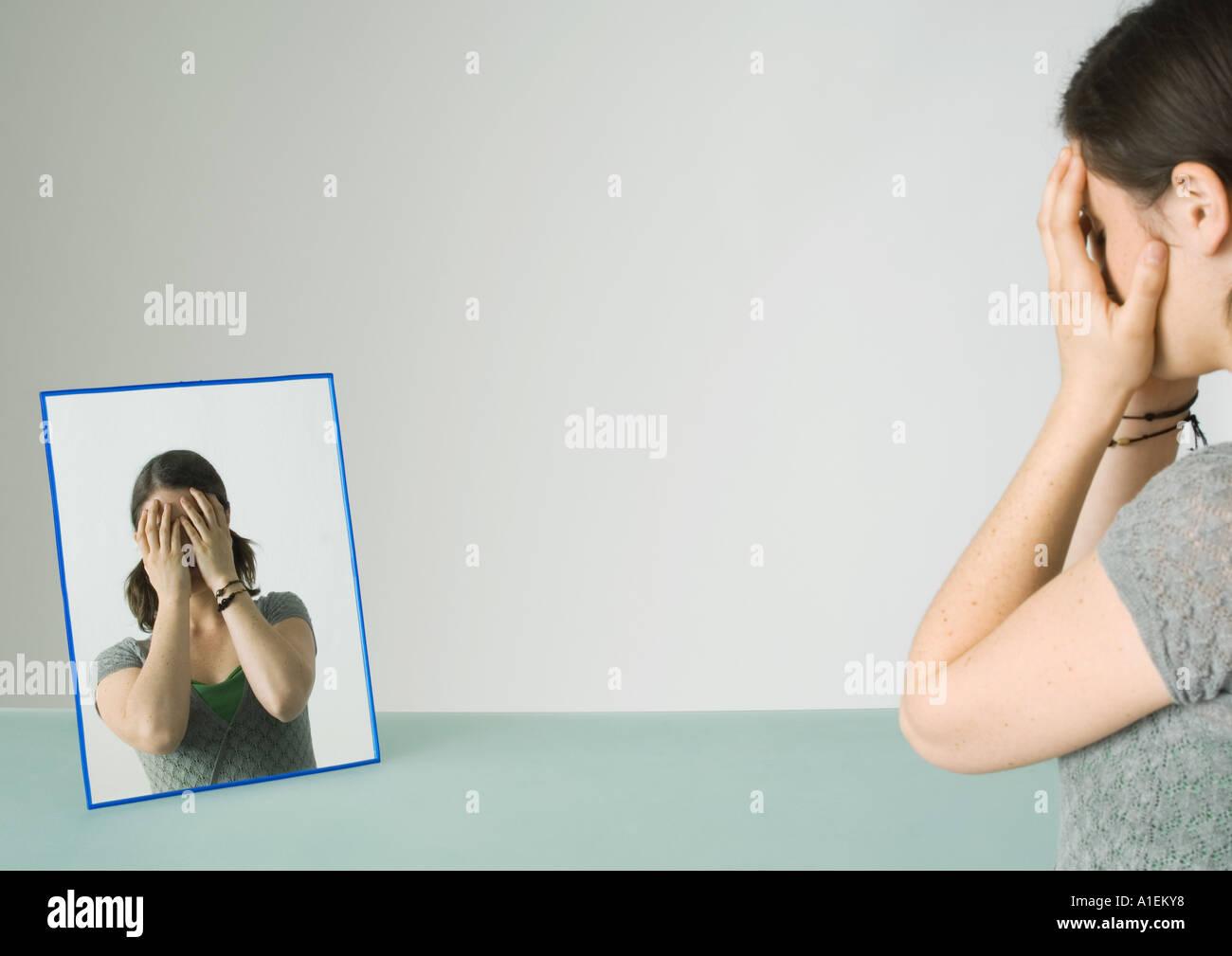 Junge Frau vor Spiegel mit Händen über Gesicht Stockbild