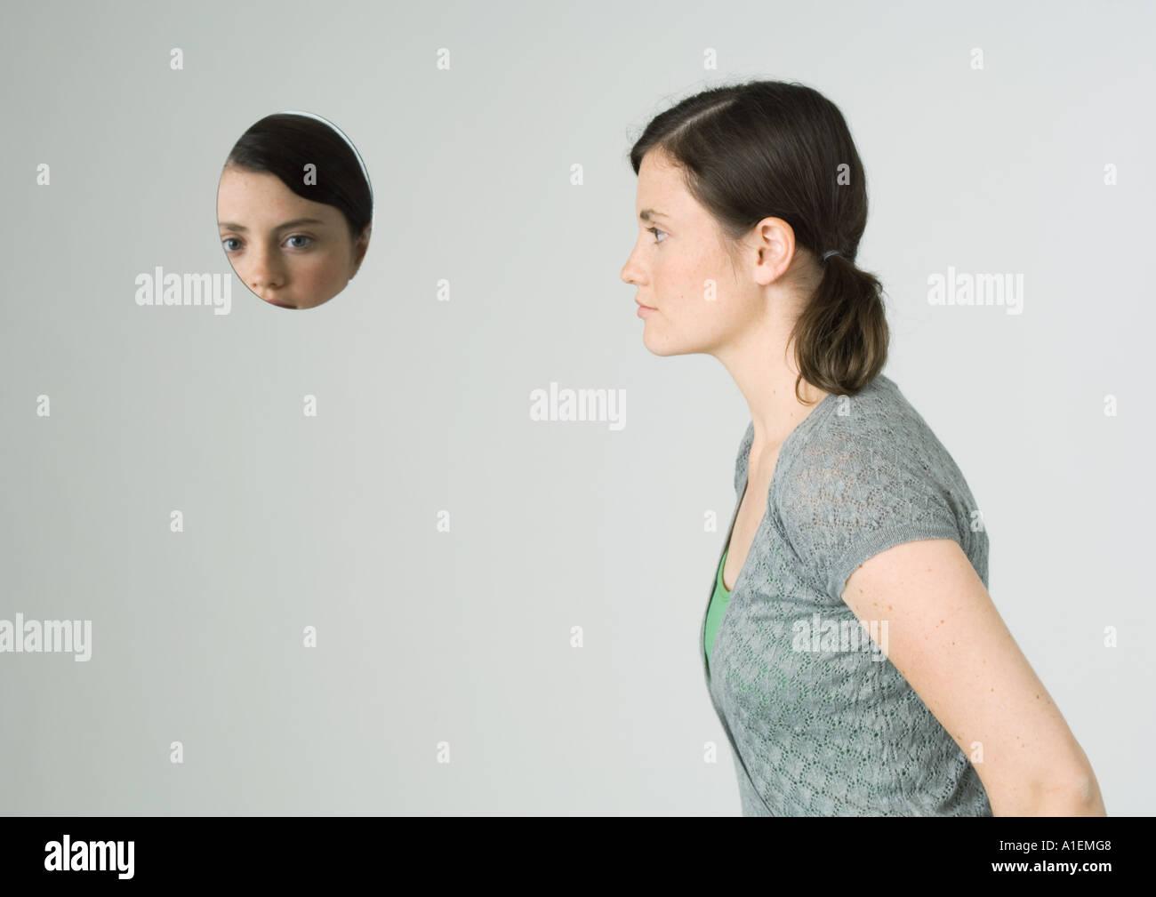 Junge Frau und Gesicht spiegeln sich im Spiegel Stockbild