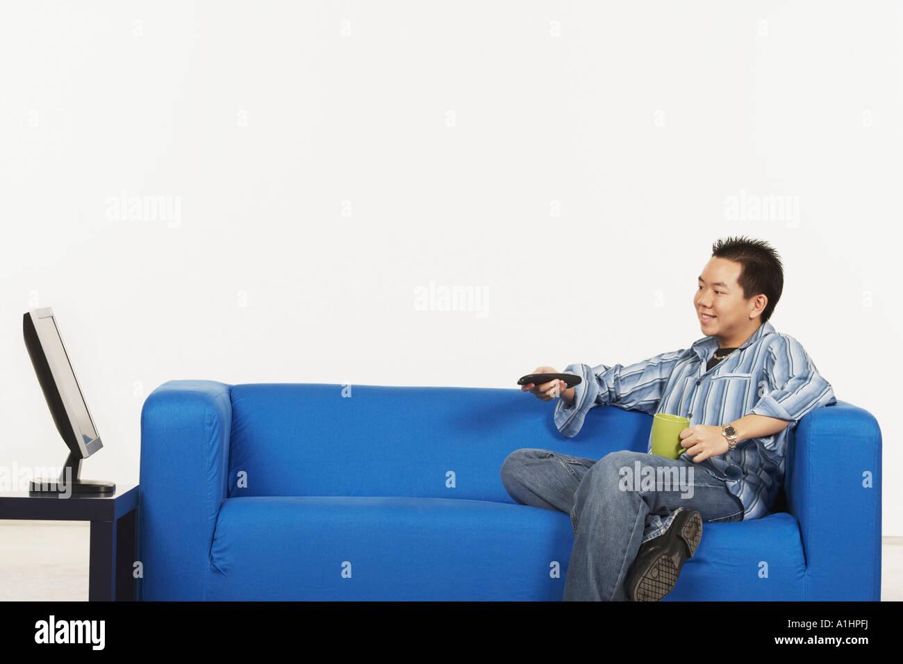 Seitenansicht eines jungen Mannes mit einer Fernbedienung sitzt vor einem LCD-monitor Stockbild