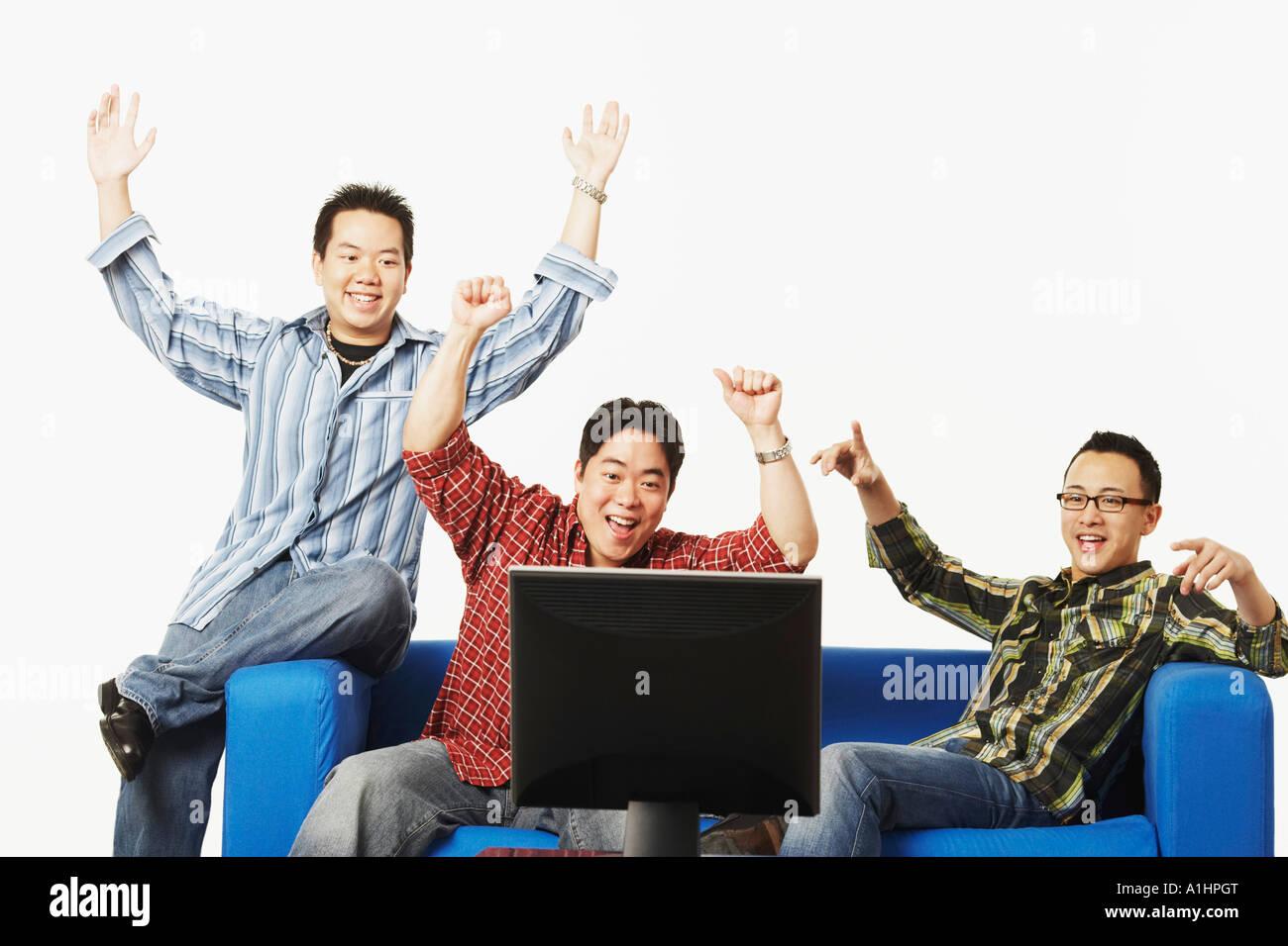 Nahaufnahme von drei jungen Männern, die jubeln vor einem flat-Screen-monitor Stockbild