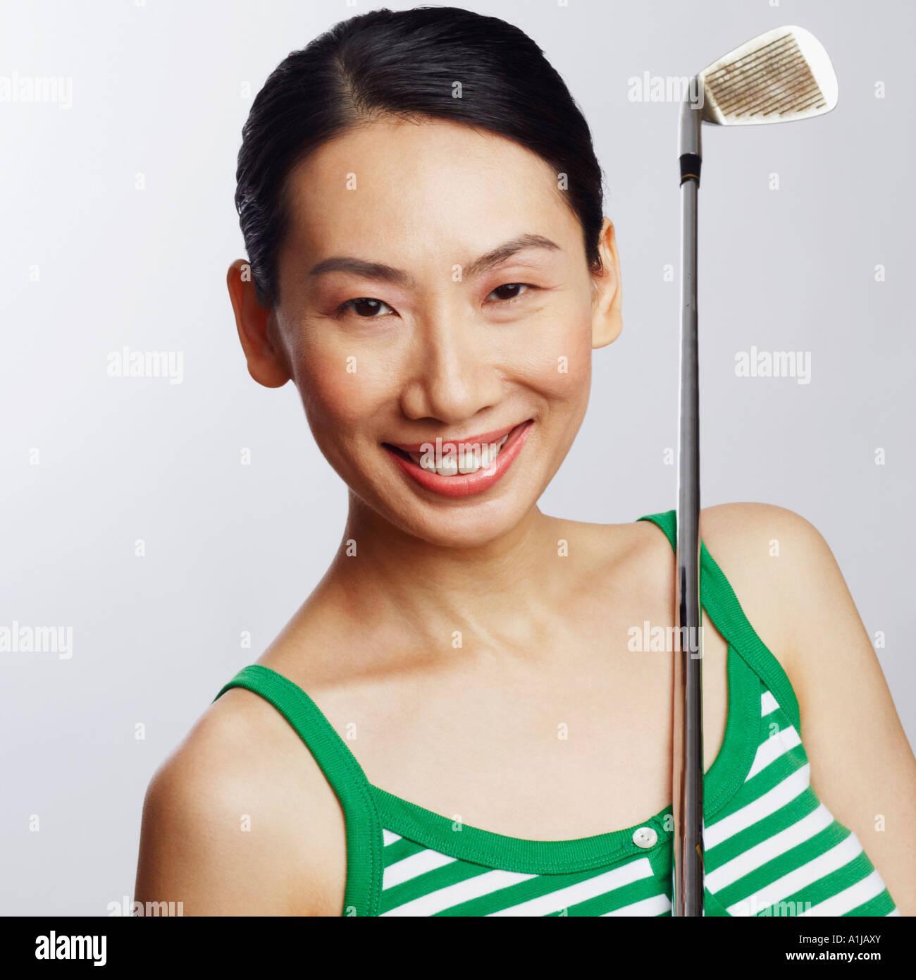 Porträt einer Mitte erwachsenen Frau hält einen Golfschläger und lächelnd Stockbild