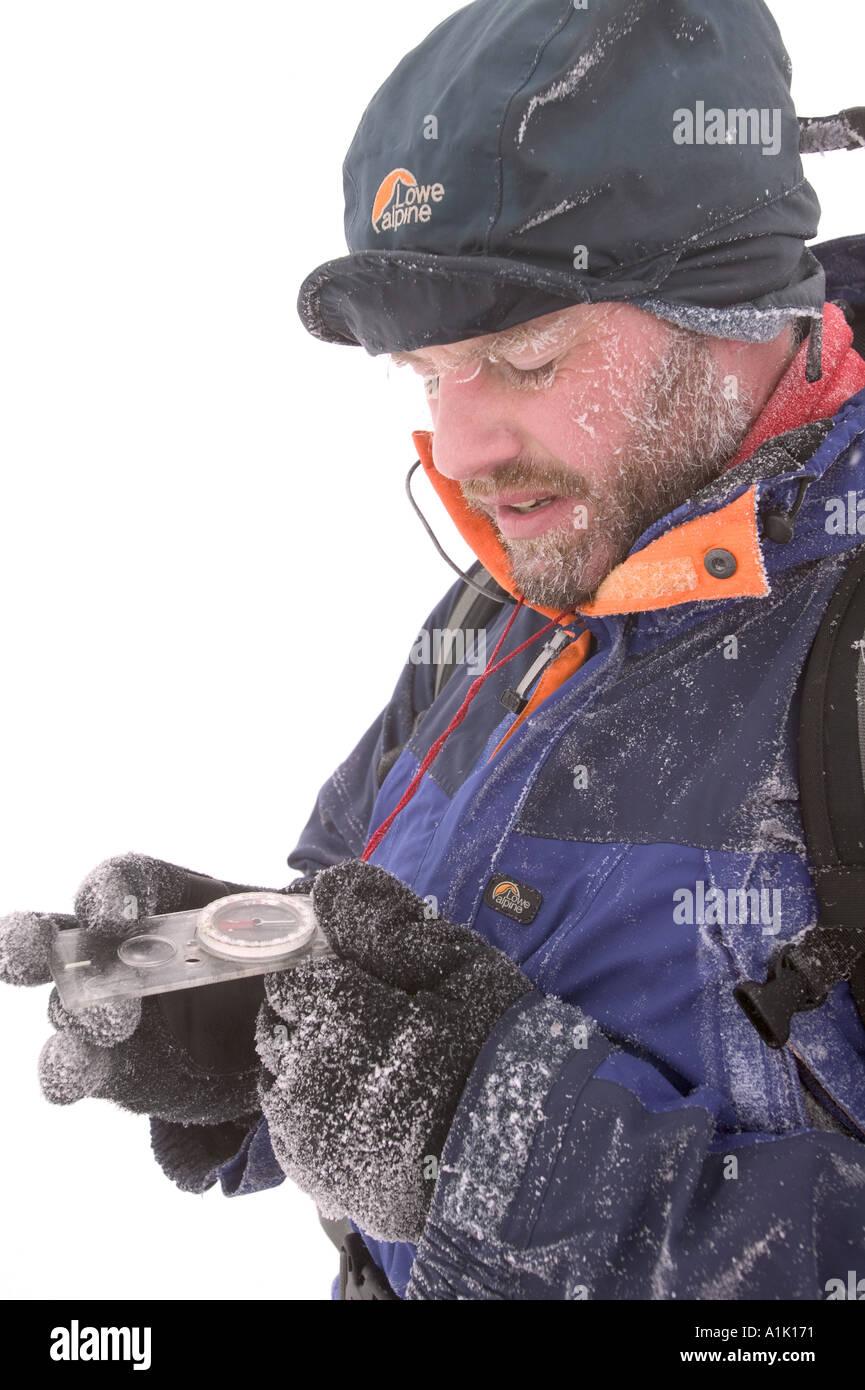 Ein Bergsteiger prüft decktest seinen Kompass mit Kletterer in Hoare Frost aufgrund extremer Kälte Stockbild