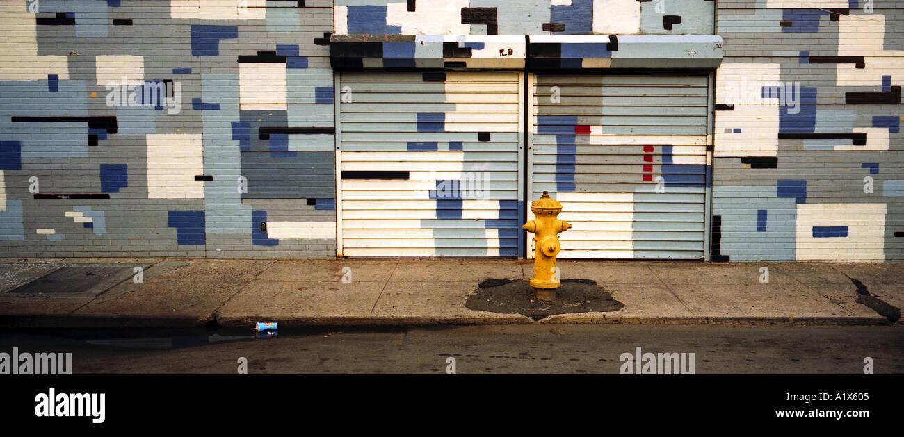 Straßenszene mit abstrakter Malerei an der Wand und Hydranten Stockbild