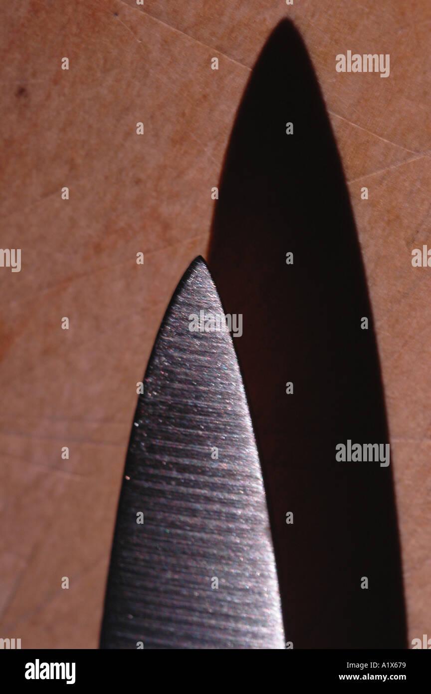scharfes Messer mit Schatten auf Schneidebrett Stockbild
