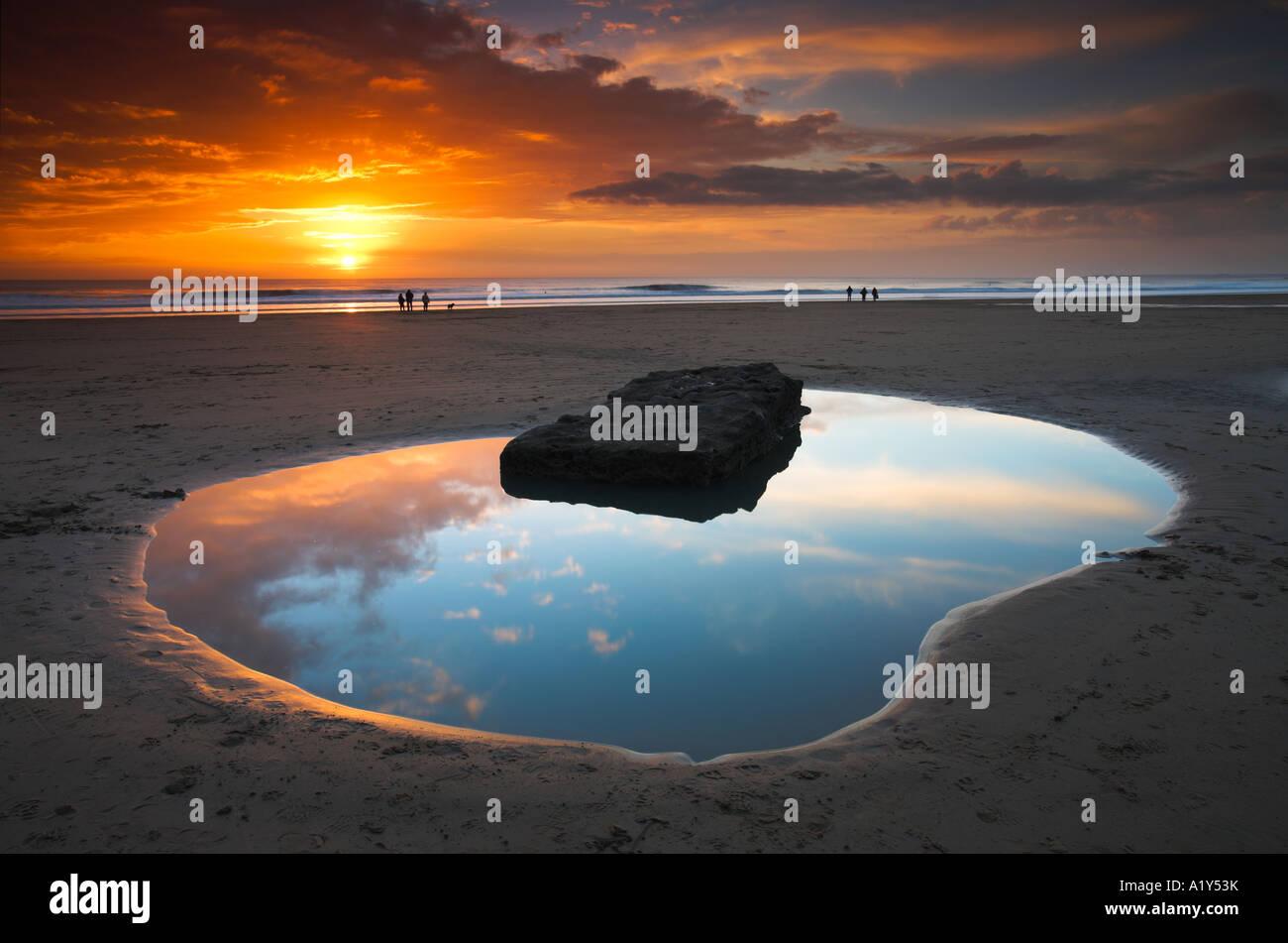 Dunraven Bay Rockpool und Menschen bei Sonnenuntergang, Southerndown, Wales Stockbild