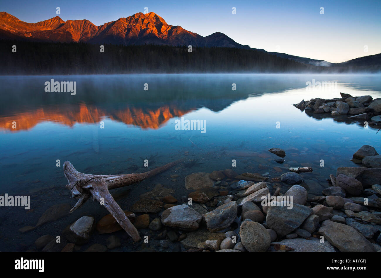Erstes Licht am Berghang über einen kalten und nebligen Patricia See, Jasper Nationalpark, Kanada Stockbild
