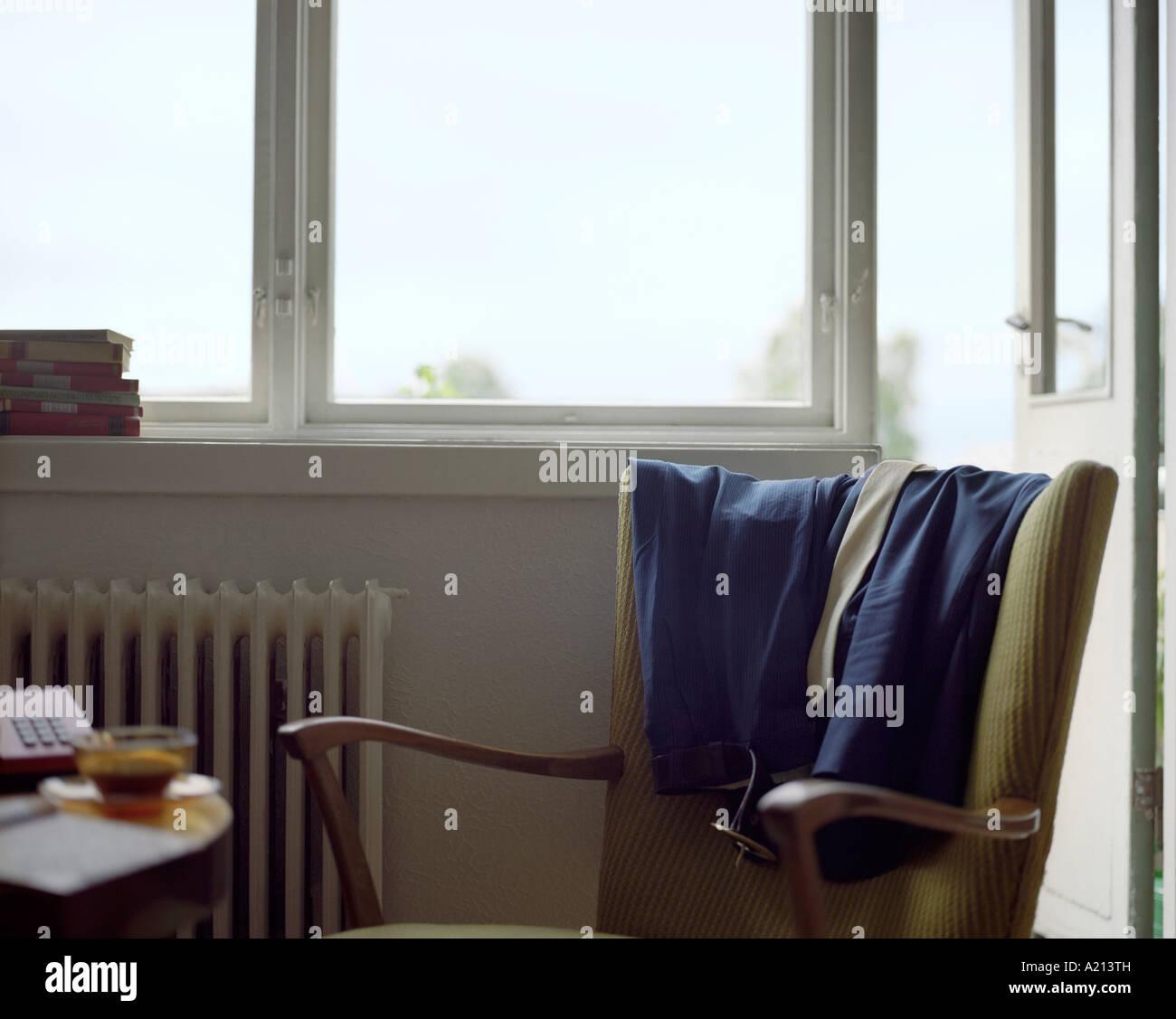 Kleidung auf Rückseite Sessel drapiert Stockbild