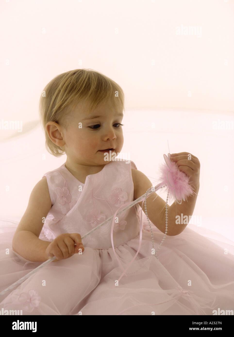 Kleinkind tragen eine rosa Party Kleid hält einen Stab Stockfoto ...
