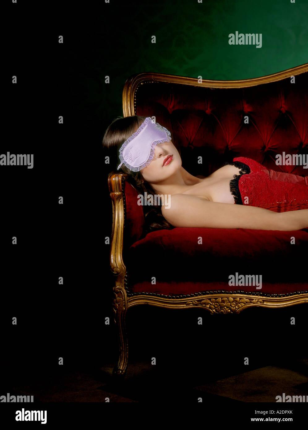 1217985 flache Innenraum Wohnzimmer junge Frau 25 30 Brünette rot Top Korsett Lüge Sofa Couch Rest entspannen Stockbild